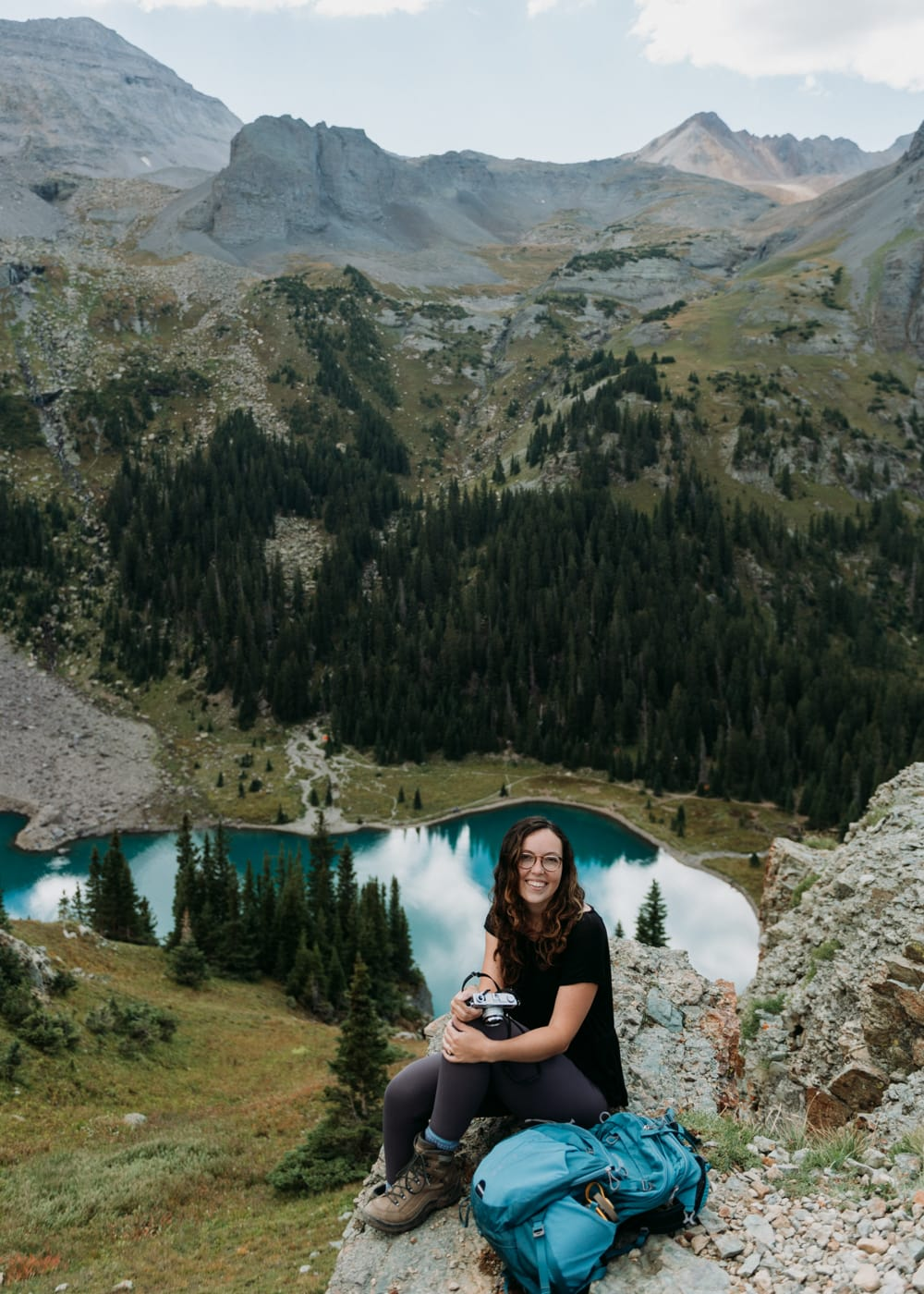 colorado elopement photographer sitting on the edge of a cliff over a turquoise blue lake in Telluride, Colorado